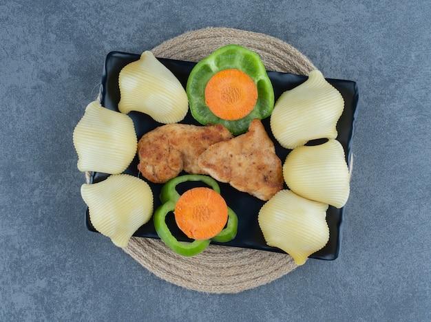 Жареные куриные наггетсы и отварной картофель на черной тарелке.
