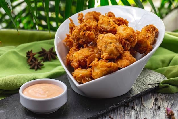 Жареные куриные наггетсы в миске с крекерами, специями и соусом, вид сбоку