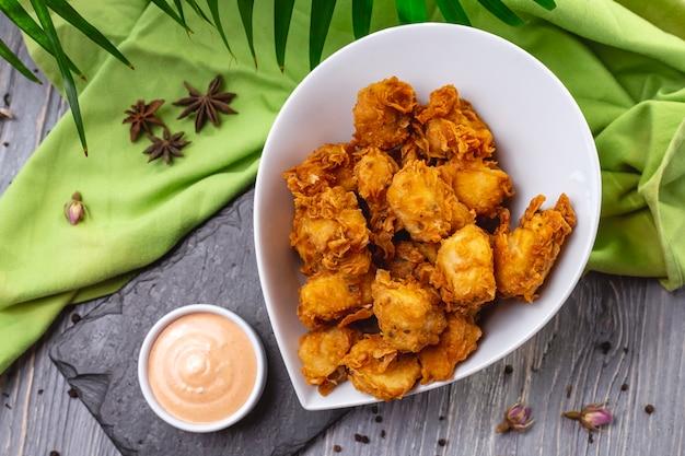Жареные куриные наггетсы в миске с крекерами, специями и соусом сверху