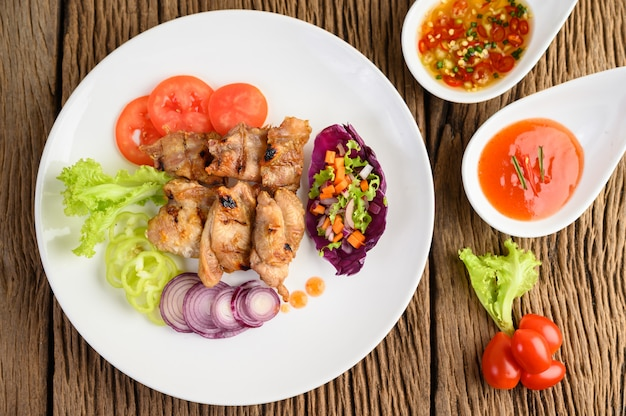 Жареная курица на белой тарелке с салатом, помидоры, перец чили нарезать на кусочки и соус на деревянный стол.