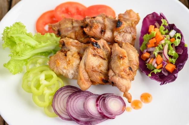 Жареная курица на белой тарелке с салатом, помидоры, красный лук и перец чили нарезать на кусочки на деревянный стол.