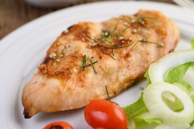 トマト、サラダ、タマネギの白い皿に鶏のグリル。