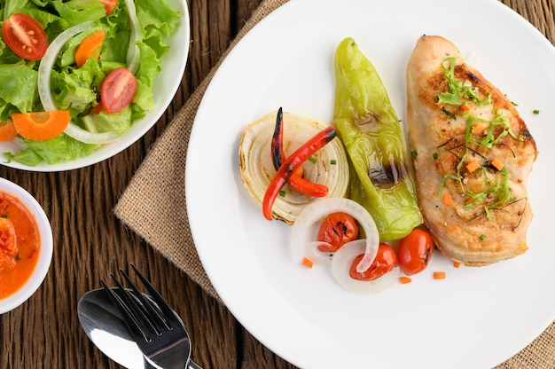 トマト、サラダ、タマネギ、チリ、ソースの白い皿に鶏のグリル。