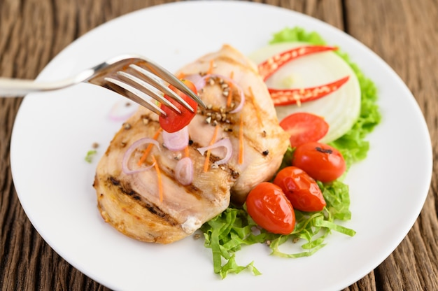 토마토, 샐러드, 양파, 칠리 소스와 함께 하얀 접시에 구운 된 닭.