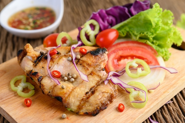 木のまな板にグリルしたチキンとサラダ、トマト、唐辛子を細かく切って、ソース。