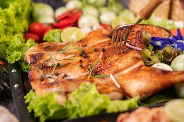 칠리와 함께 접시에 구운 된 닭고기 마늘과 후추 씨앗을 뿌리고.