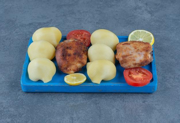 Части жареной курицы и вареный картофель на синей доске.