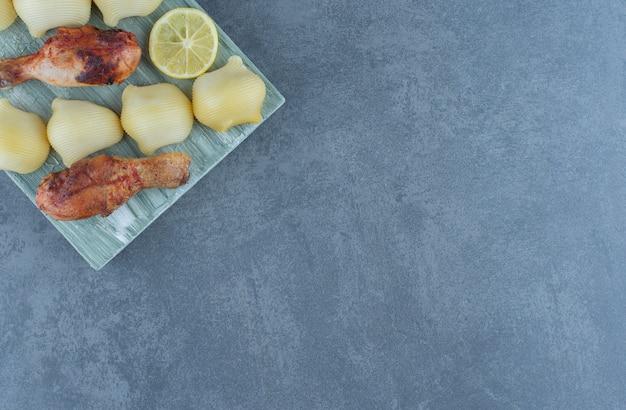 나무 판자에 구운 닭고기 부분과 삶은 감자.