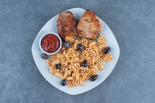 Жареные куриные части и макароны на белой тарелке.