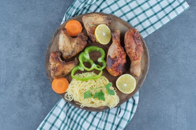 Жареные куриные части и спагетти на деревянной доске.