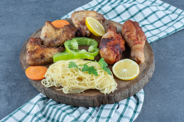 Parti di pollo alla griglia e spaghetti su un pezzo di legno.