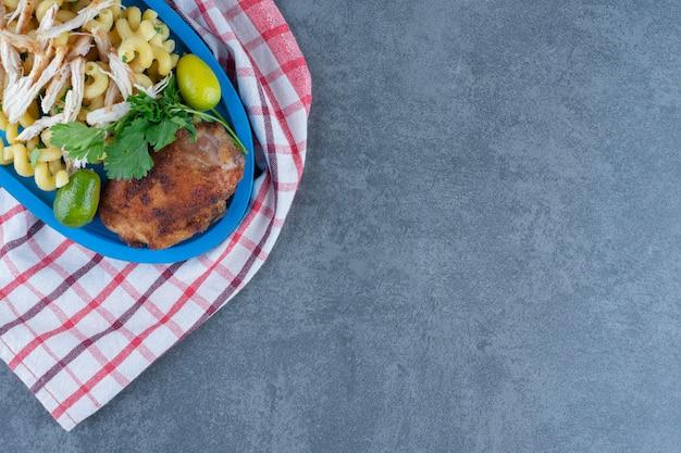 Pollo alla griglia e pasta sul piatto blu.