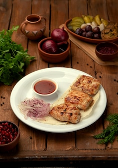 Grilled chicken pieces with ketchup and onion