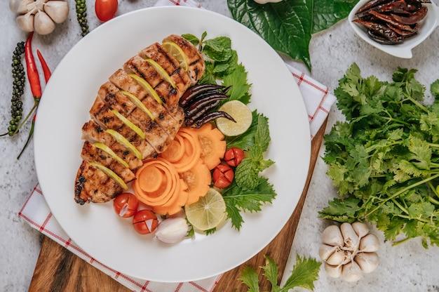 Pezzi di pollo alla griglia con pomodori, carote, peperoni fritti, cipolla rossa, cetriolo e menta.