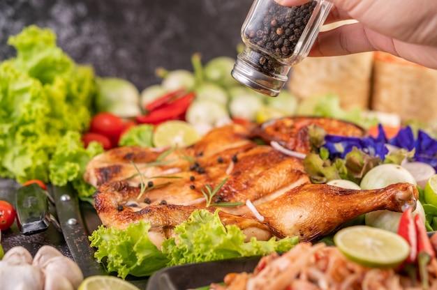 Pollo alla griglia sul piatto con peperoncino aglio e cosparso di semi di pepe.