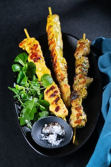 Grilled chicken and pork curry skewers, with spices, herbs on dark background