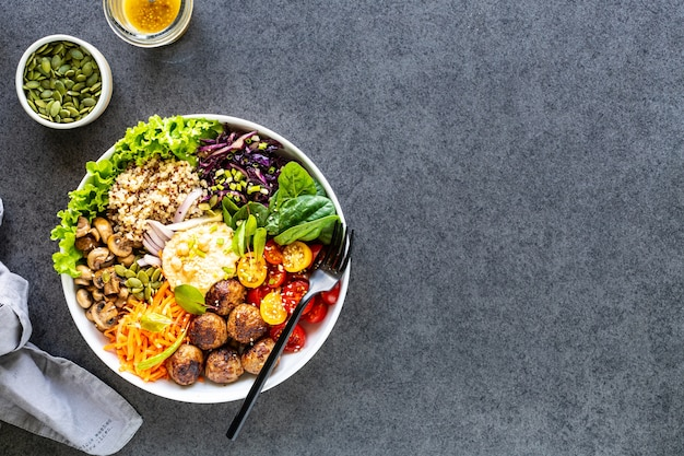 Grilled chicken, rice, spicy chickpeas, avocado, cabbage, pepper buddha bowl on dark surface, top view. delicious balanced food concept