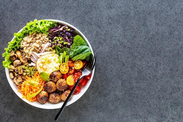 Grilled chicken, rice, spicy chickpeas, avocado, cabbage, pepper buddha bowl on dark, top view.