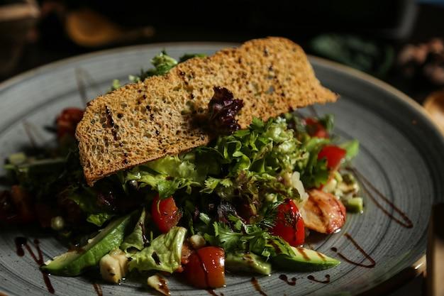 Grilled chicken salad lettuce avocado greens tomato