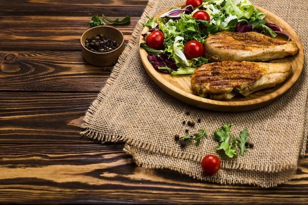 Pollo alla griglia e insalata vicino pepe nero