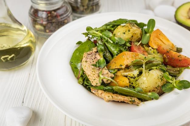 Жареный куриный салат, помидоры, картофель и зелень на белой тарелке и белом столе