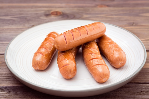 Grilled chicken sausages ready to eat on a plate on a wooden table