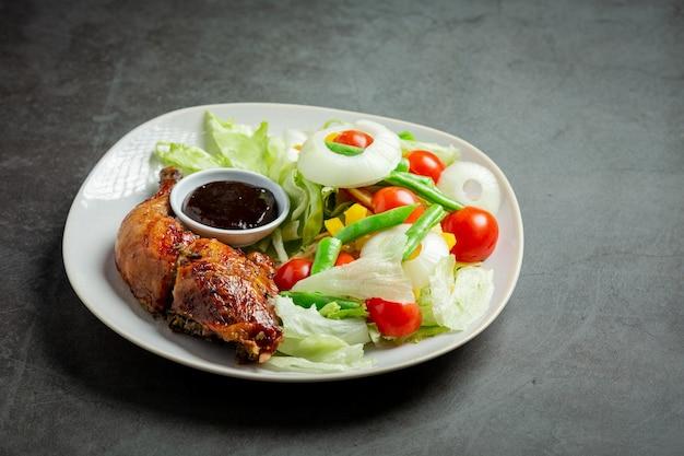 Куриный стейк на гриле и овощи на темном фоне