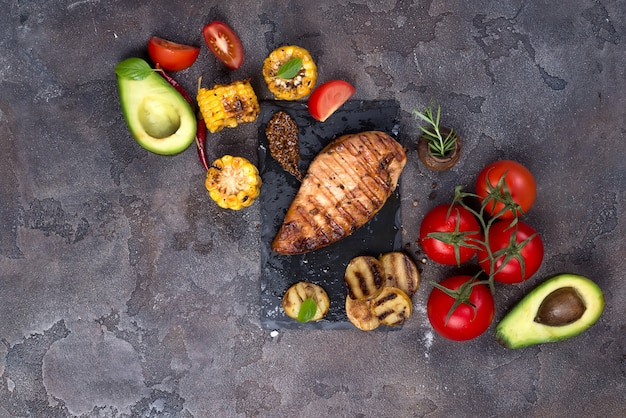 Grilled chicken steak and vegetable, baked potatoes and corn on dark background