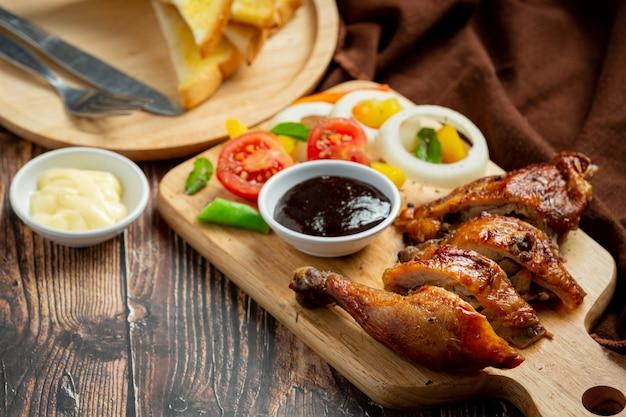 Bistecca di pollo alla griglia e verdure su fondo di legno scuro