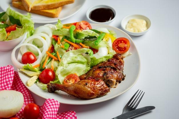 Bistecca di pollo alla griglia e verdure su fondo di marmo