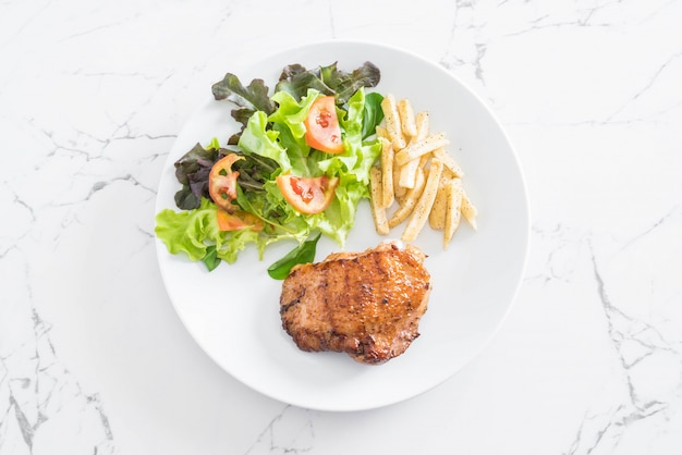 Grilled chicken steak with french fries and vegetable salad
