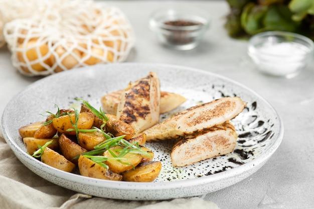 Куриный стейк на гриле с картофельным идахо на керамической тарелке с ингредиентами на бетонном столе.
