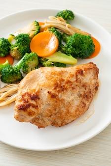 Жареный куриный стейк с овощами на белой тарелке