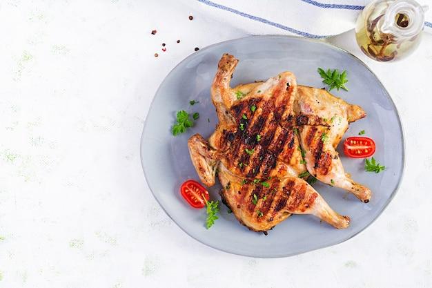 Жареный цыпленок табака на синей тарелке. грузинская кухня. вид сверху, вверху