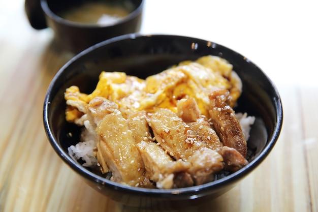 Жареный цыпленок с рисом терияки и яйцом на деревянном фоне