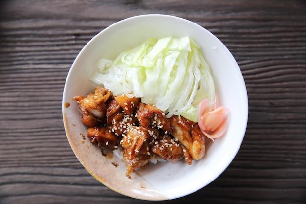 木の背景に鶏の照り焼きご飯、日本食