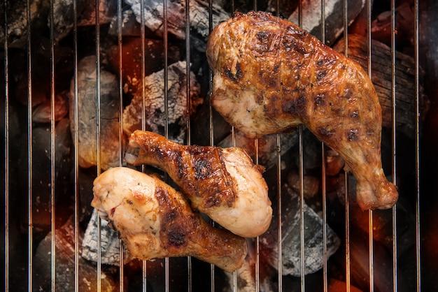 バーベキューの炎の上の鶏もも肉のグリル