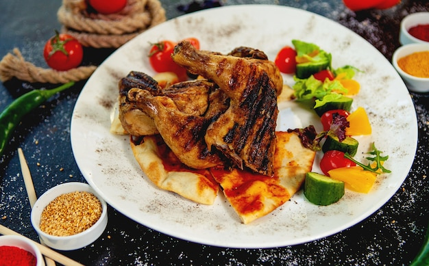 Grilled chicken thighs on pita bread served with fresh vegetables