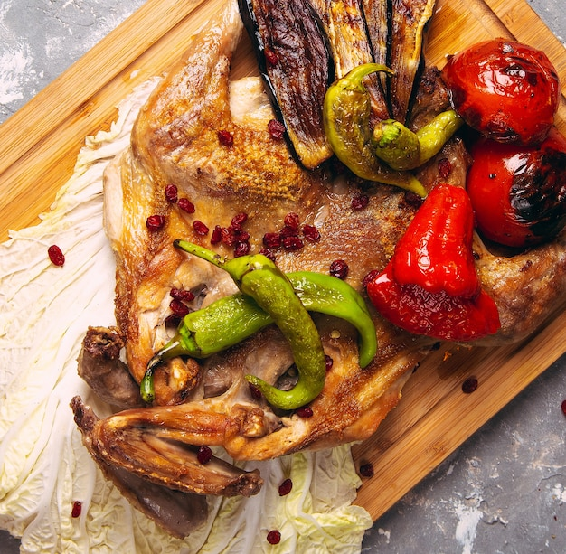 Grilled chicken and vegetables on the wooden board close-up. horizontal view from above