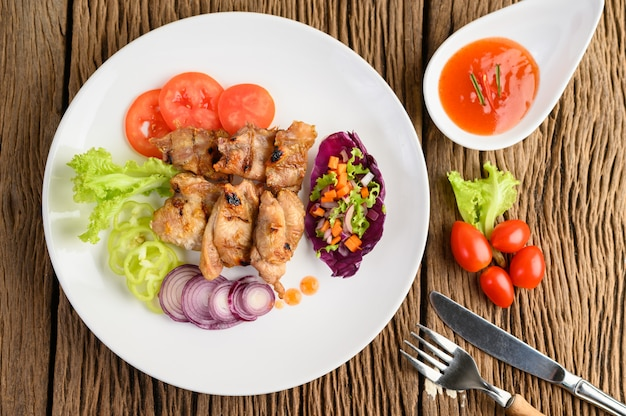 Grilled chicken on a white plate with a salad, tomatoes, chilies cut into pieces and sauce on wooden table.