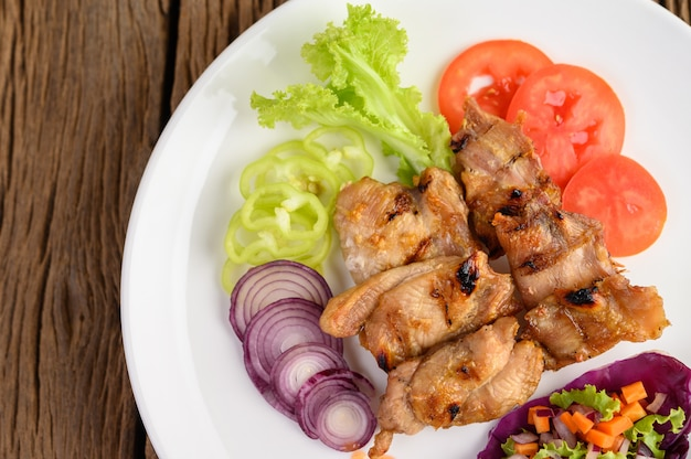 Grilled chicken on a white plate with a salad, tomatoes, red onion, and chilies cut into pieces on wooden table.