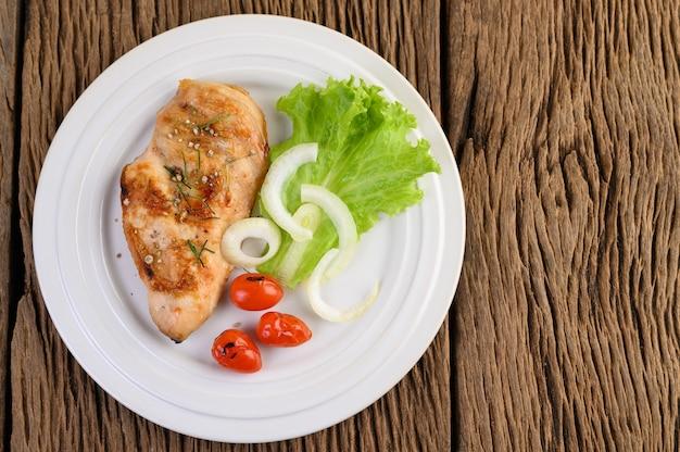 Pollo alla griglia su un piatto bianco con pomodori, insalata e cipolla.
