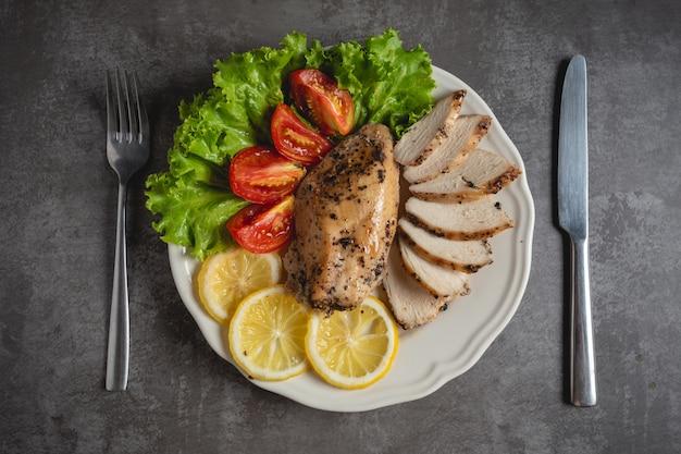 Pollo alla griglia su un piatto bianco.
