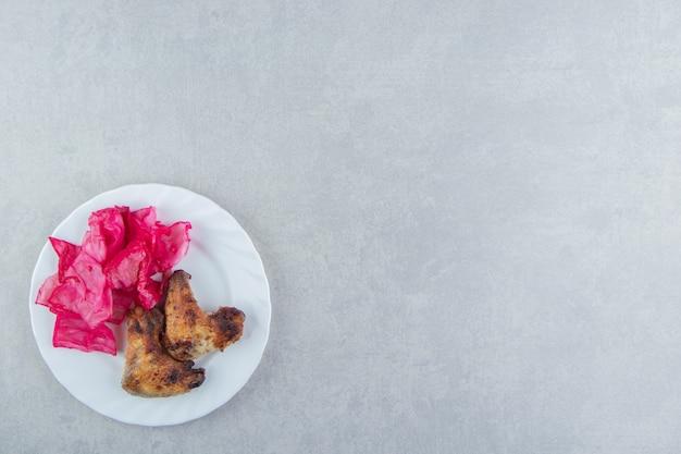 Жареные куриные крылышки и капуста на белой тарелке.