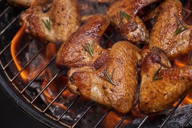 Куриные крылышки гриль на пламенном гриле с овощами гриль в соусе барбекю с перцем розмарином, солью.