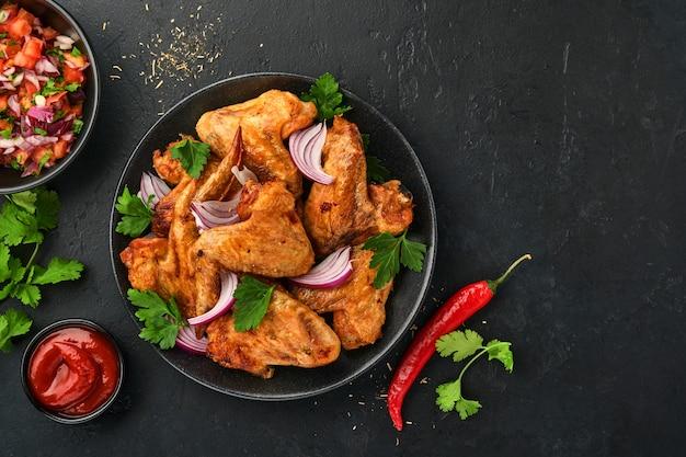 Куриные крылышки на гриле или жареный барбекю со специями и томатным соусом сальса на черной тарелке. вид сверху с копией пространства.