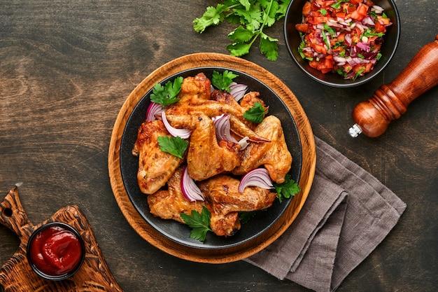 구운 닭 날개 또는 검은 접시에 향신료와 토마토 살사 소스를 곁들인 구운 바베큐. 복사 공간이있는 상위 뷰.