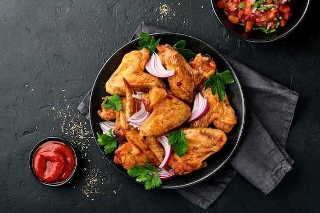 Жареные куриные крылышки или жареный барбекю со специями и томатным соусом сальса на черной тарелке.