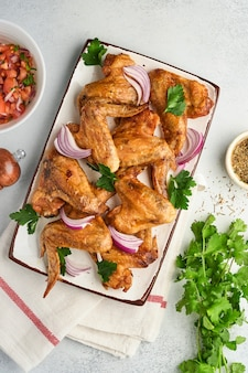 Куриные крылышки на гриле или жареный барбекю со специями и томатным соусом сальса на тарелке на светло-сером фоне из сланца, камня или бетона. вид сверху с копией пространства.
