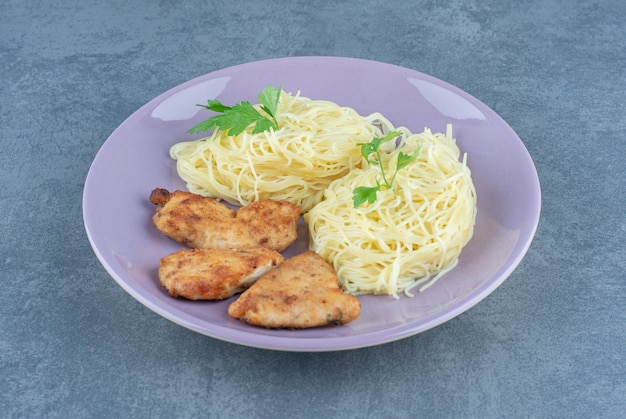 Grilled chicken wings and spaghetti on purple plate.